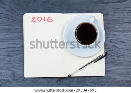 2016 planning agenda. Book with cup of coffee on wood background. - stock photo