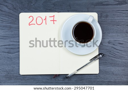 2017 planning agenda. Book with cup of coffee on wood background. - stock photo
