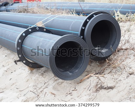 plastic pipes on sand background - stock photo