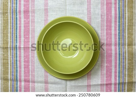plate on linen tablecloth - stock photo
