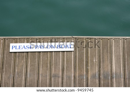 'Please pay on the boat' sign on a wooden jetty
