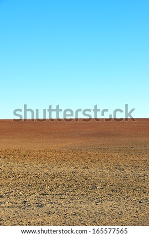 plowed soil of agricultural field against blue sky