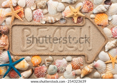 Pointer made of rope with an inscription beach, with sea shells and starfish, on sand - stock photo