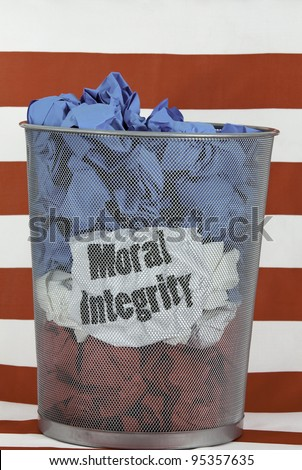 Political Problem. Mesh trash can full of red, white and blue wads of paper showing Moral Integrity is in the garbage.