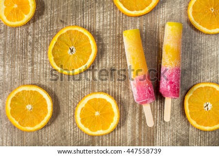 Popsicles with sliced orange fruit on wooden background. Top-view. - stock photo