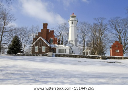 """Port Sanilac Winter"" -- All is quiet at the Port Sanilac Lighthouse during a cold but sunny winter's day. - stock photo"