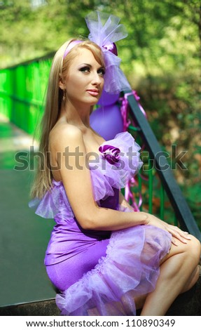 Portrait glamorous young blonde girl,posing in violet dress on the green bridge