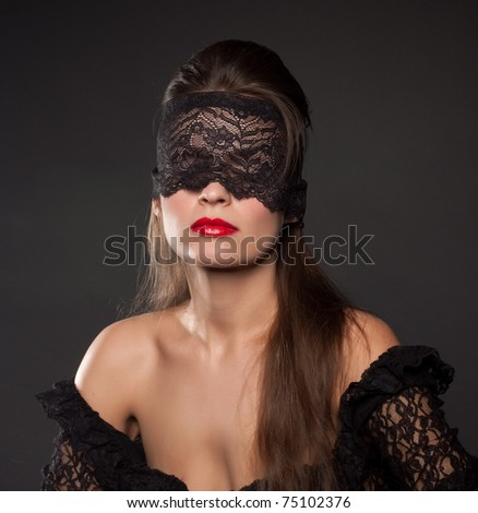 .Portrait of a beautiful brunette with lacy blindfolded, closeup - stock photo
