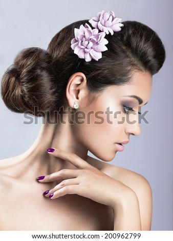Portrait of a beautiful girl with perfect skin and purple flowers on her head. Photo shot in the Studio on a grey background - stock photo