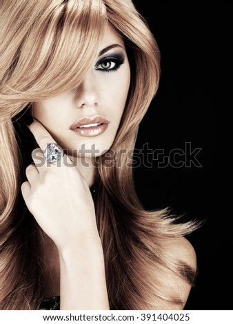 portrait of a beautiful woman with long red hairs and blue fashion eye makeup with blue ring on finger  -  on black background