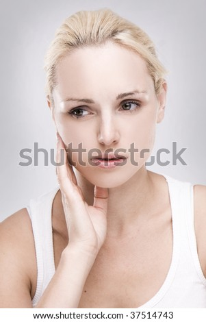 portrait of a caucasian blonde woman with toothache on grey background - stock photo