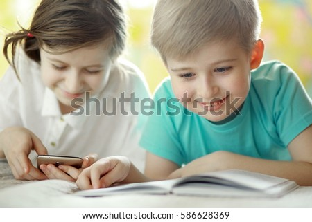 Portrait of a cheerful boy with a book. Girl using smart phone in the background