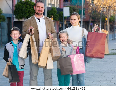 Portrait of a family of four people happily shopping together in the city in summer - stock photo