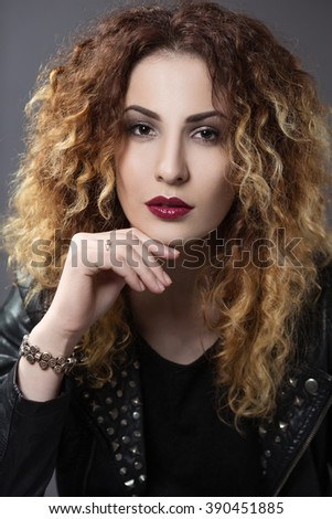 portrait of a gorgeous red-haired woman with curly hair in the style of glam rock - stock photo