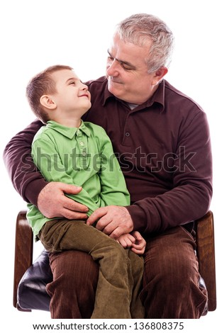Portrait of a grandfather with his happy grandson sitting in armchair isolated on white background - stock photo