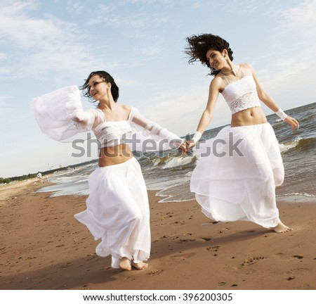 Portrait of a happy young girls together on the beach
