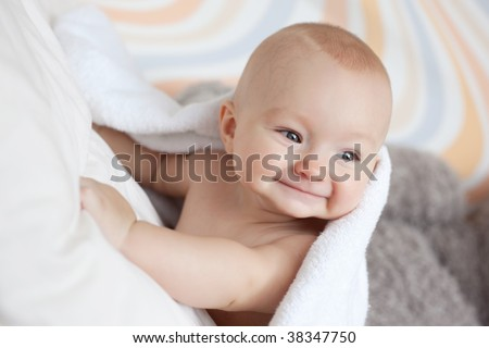 Portrait of a lovely baby covered with white towel