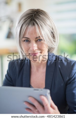 portrait of a senior businesswoman of fifty years old working at office with a tablet. she is a business woman. she is smiling and looking at camera, she wears a blue jacket