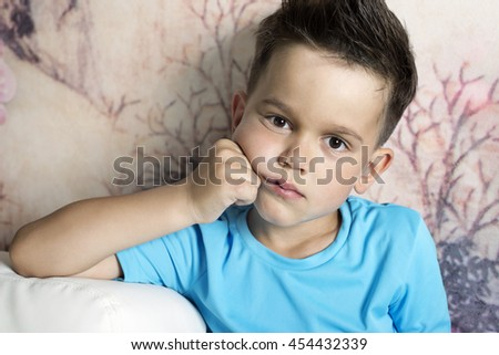 Portrait of a 6 year old boy with a sad look closeup - stock photo