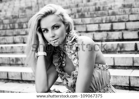 Portrait of a Young caucasian woman sitting on the ladder of old european city. Outdoors - stock photo