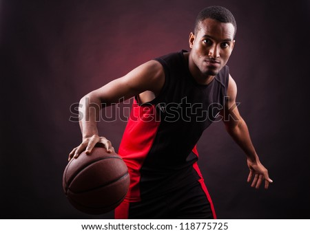 Portrait of a young male basketball player against black background - stock photo