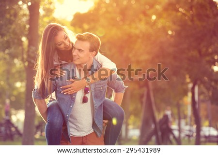 portrait of a young man giving piggyback in summer  - stock photo