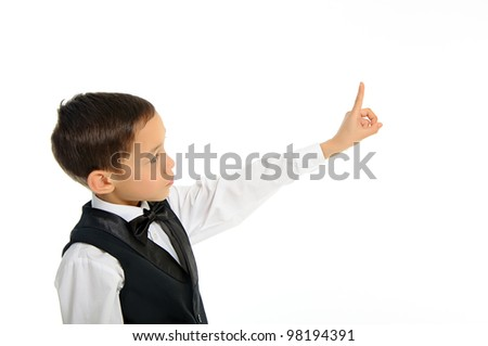 Portrait of a young school boy in black suit touching something with his finger isolated on white - stock photo