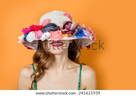 Portrait of attractive elegant woman in flowers hat over bright background - stock photo