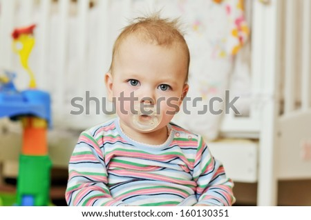 portrait of  baby with dummy at home - stock photo