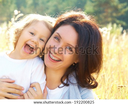 Portrait of  beautiful young woman hugging her little girl