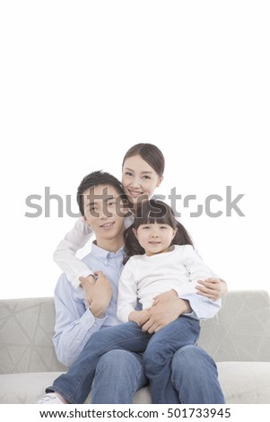 Portrait of father sitting on sofa,daughter sitting on father's leg, mother behind