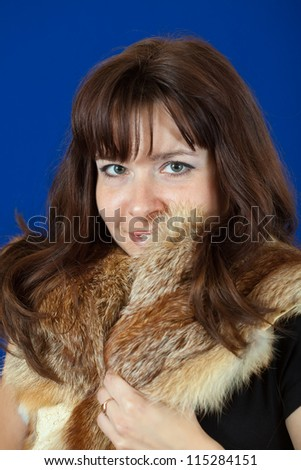 portrait of  girl in fox fur over blue background - stock photo