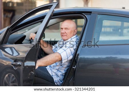 Portrait of  gray-haired man in  car. - stock photo
