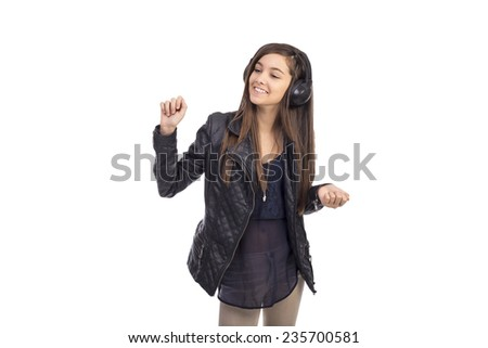 Portrait of happy cute  teenage girl  listening music on her headphones and dancing isolated on white background - stock photo