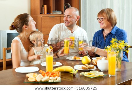 Portrait of  happy three generations family eating  fresh ripe friuts with juice at home