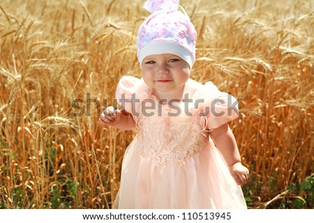 Portrait of little child girl in wheat field alone, in white hat