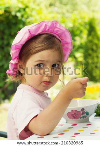 portrait of little cute girl in a purpule cap eats with appetite a breakfast from a plate with the drawn flower in outdoor cafe  - stock photo