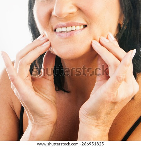 Portrait of mature beautiful woman massaging her face isolated on white background - stock photo
