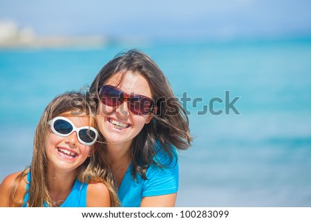 portrait of mother and her daughter having fun on tropical beach - stock photo