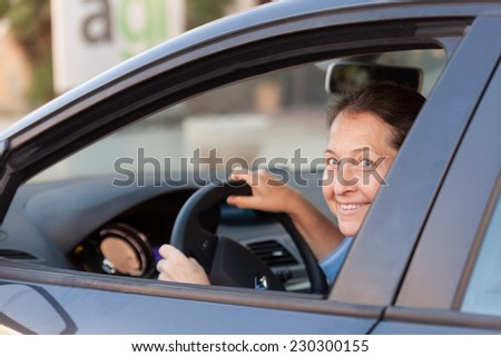 Portrait of senior woman in  black car. - stock photo