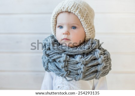 portrait of stylish pretty nice baby girl in wool snood and hat, tall boots and modern dress staying on white background and wooden floor watching aside - stock photo