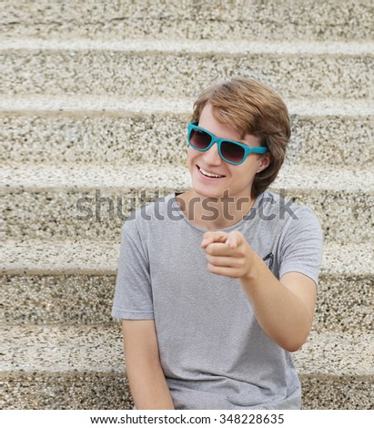 Portrait of  teenage boy pointing at the camera. - stock photo