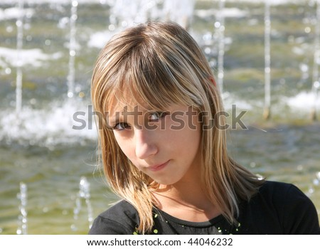 Portrait of the  beautiful girl  at a fountain