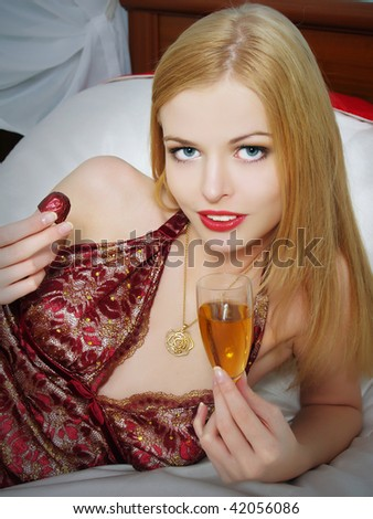 Portrait of the beautiful girl lying on a bed with wine