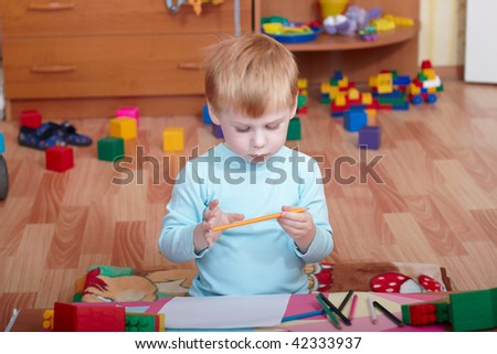 Portrait of the little boy in a children's room - stock photo
