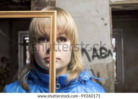 Portrait of the young blonde with a frame for a picture