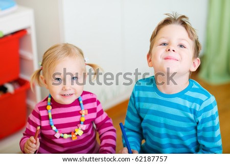 Portrait of two little kids drawing at home - stock photo