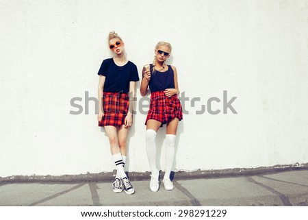portrait of two pretty hipster blonde sisters  wearing plaid skirt and  black T-shirt. Girls smile, have fun against  urban white wall. - stock photo