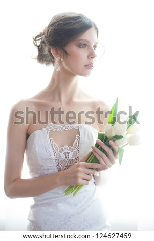 Portrait of young beautiful bride with bouquet of white tulips in her wedding day - stock photo