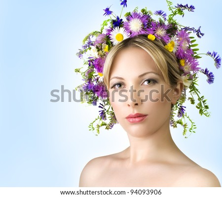 Portrait of young beautiful woman with   flower in long blond hair - stock photo